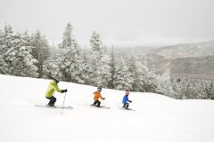 family of skiers descend a trail